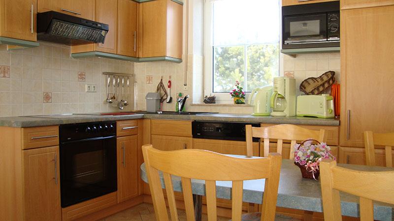 Die qualitativ hochwertige Küche ist im amerikanischen Stil zum Wohnzimmer hin offen. Zur Ausstattung gehören Kühlschrank mit Gefrierfach, Geschirrspüler, Mikrowelle und ein Ceranfeldkochherd mit Backofen.
